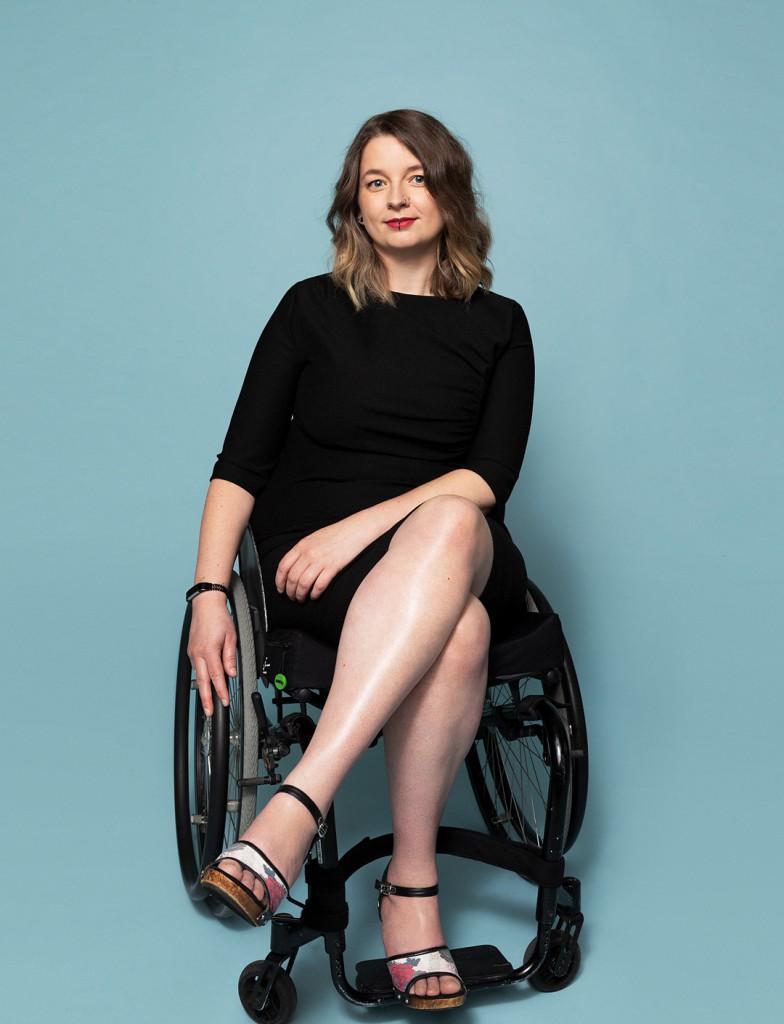 Jacqueline in zwarte jurk in rolstoel met blauwe achtergrond